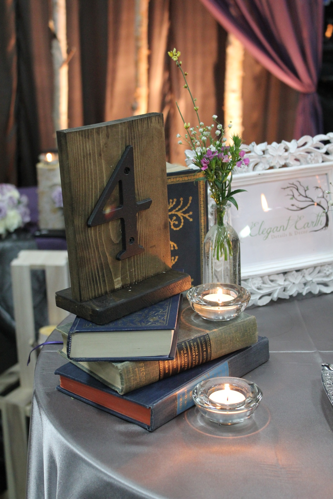 A stack of books topped with a rustic table number. We added a vial of bright wildflowers and candles to compliment the darker tones.