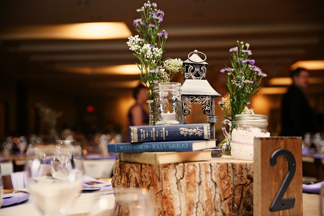 Pretty lanterns, summer flowers, and books give the guest tables colour, warmth and an antiquey vibe.