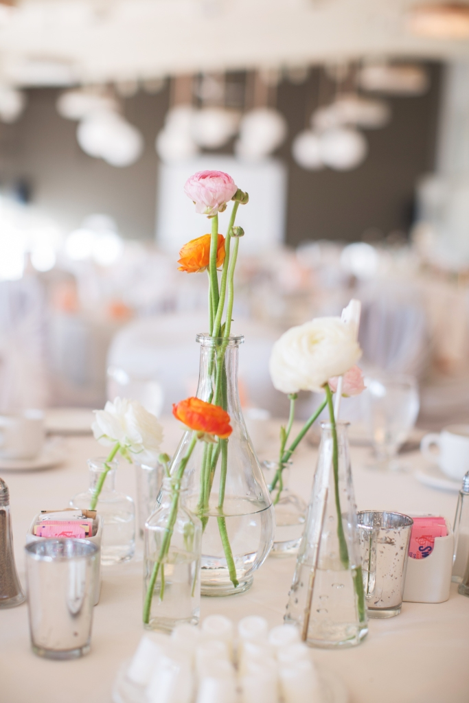 Ranunculus flowers in a variety of glass vases and vials creates a bright and airy centerpieces. We added candles in silver  votive cups for a pretty glow after dusk.