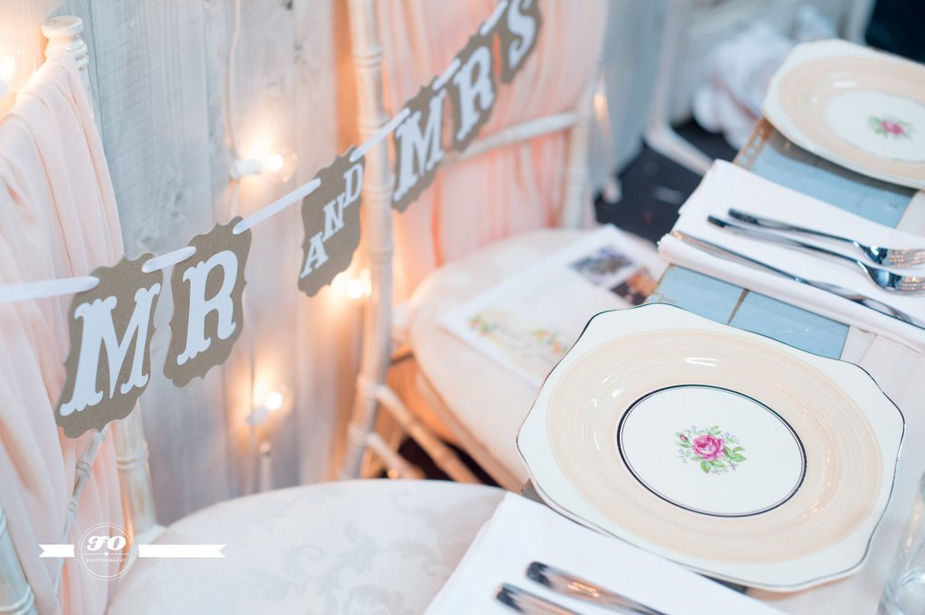 Sweetheart table details: Antique plates, an antique table, and luxurious fabric for the new Mr. & Mrs.