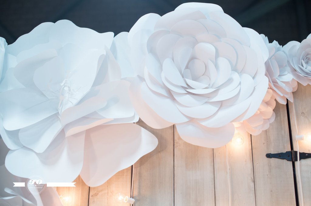Hand-crafted paper flowers border our white barn wood backdrop.