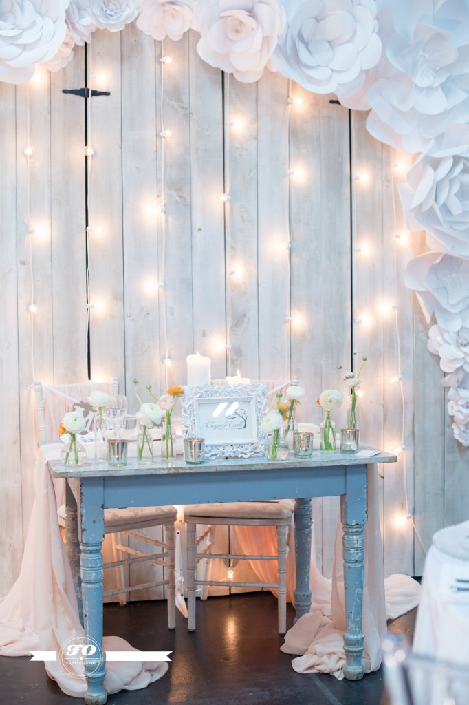 White-washed barn wood, framed by paper flowers, and dripping with lights and romance.